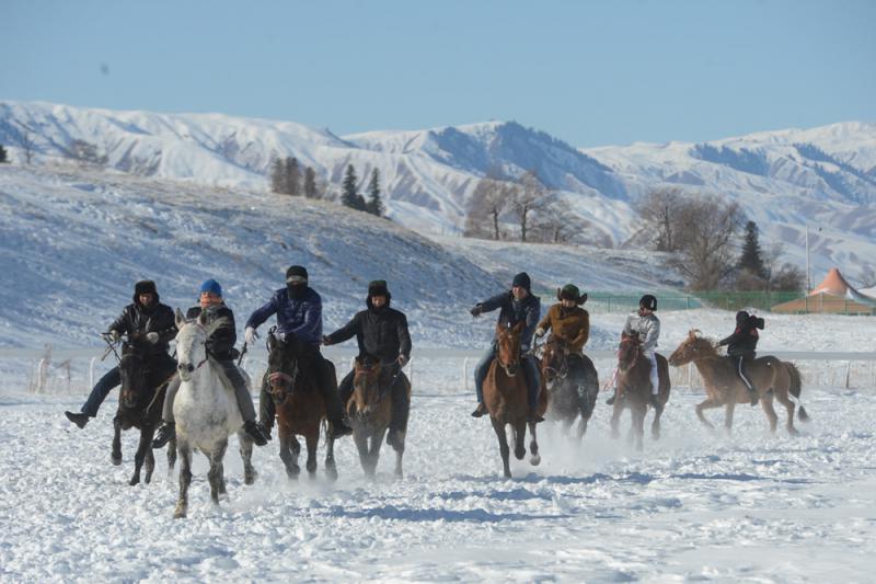 图:17日,新疆新源县那拉提旅游风景区的当地居民在雪地上进行赛马比赛